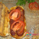 After the soujouk is grilled open it up and add the slices of tomatoes and pickles.